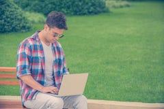 Giovane che si siede sul banco nel parco e che lavora al computer portatile fuori Immagini Stock Libere da Diritti