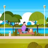 Giovane che si siede sul banco in parco facendo uso del computer portatile all'aperto illustrazione di stock