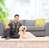 Giovane che si siede sul pavimento con il suo cane a casa Fotografie Stock