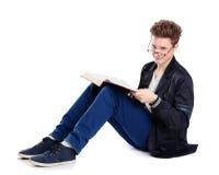 Giovane che si siede sul pavimento e che legge un libro Fotografia Stock