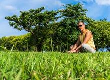 Giovane che si siede sull'erba e che lavora con il computer portatile Fotografia Stock Libera da Diritti