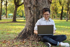 Giovane che si siede sull'erba verde e che gode con il computer portatile nel parco Fotografie Stock Libere da Diritti
