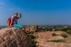 Giovane che si siede sulla montagna, enjoing la vista dopo il trekking Immagine Stock