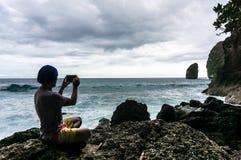 Giovane che si siede sulla roccia e che fa una foto delle onde Fotografia Stock