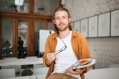 Giovane che si siede sulla tavola in ufficio con i vetri ed il caso del documento in mani Ritratto del ragazzo sorridente con cap Immagini Stock