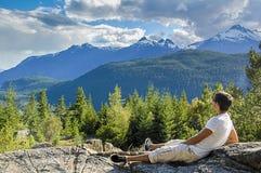 Giovane che si siede sulle rocce che esaminano le montagne Fotografia Stock