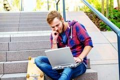 Giovane che si siede sulle scale e che per mezzo del computer portatile Immagini Stock Libere da Diritti