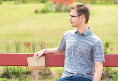 Giovane che si siede un banco e che tiene un libro Fotografia Stock