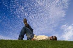 Giovane che si trova giù sull'erba Fotografia Stock