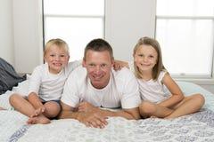 Giovane che si trova sul letto insieme ai suoi piccoli del figlio dei dolci 3 e 7 anni e figlia che giocano i bambini in famiglia Fotografia Stock