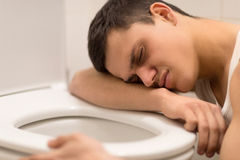 Giovane che si trova sul sedile di toilette. Fotografia Stock Libera da Diritti