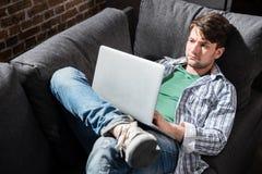 Giovane che si trova sul sofà e che per mezzo del computer portatile a casa, piccola gente di affari di concetto Fotografia Stock