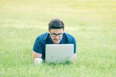 Giovane che si trova sull'erba e che per mezzo del computer portatile Fotografia Stock
