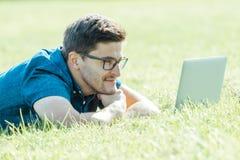 Giovane che si trova sull'erba e che per mezzo del computer portatile Immagini Stock