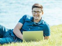Giovane che si trova sull'erba e che per mezzo del computer portatile Fotografia Stock Libera da Diritti