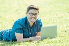 Giovane che si trova sull'erba e che per mezzo del computer portatile Immagine Stock