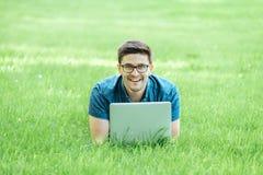 Giovane che si trova sull'erba e che per mezzo del computer portatile Immagine Stock Libera da Diritti