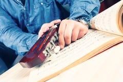 Giovane che sintonizza una chitarra Fotografia Stock Libera da Diritti