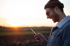 Giovane che sorride con lo smartphone in sue mani sui precedenti del tramonto immagine stock