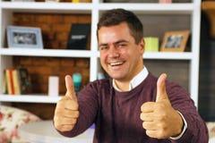Giovane che sorride e che mostra due pollici su Immagine Stock