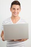 Giovane che sorride e che per mezzo di un computer portatile Fotografia Stock