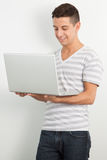 Giovane che sorride e che per mezzo di un computer portatile Immagine Stock