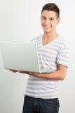 Giovane che sorride e che per mezzo di un computer portatile Fotografia Stock Libera da Diritti