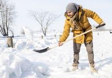 Giovane che spala neve nel paese Fotografia Stock