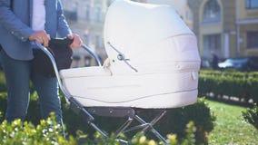 Giovane che spinge la carrozzina del bambino che cammina nel parco, prendente cura dell'infante, paternità video d archivio