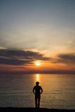 Giovane che sta alla spiaggia davanti alla vista stupefacente del mare al tramonto o all'alba e che pensa al suo futuro rear Fotografia Stock Libera da Diritti