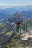 Giovane che sta alle montagne di Dachstein dell'austriaco della piattaforma di vista Fotografia Stock
