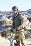 Giovane che sta con il mountain bike contro le colline Immagini Stock Libere da Diritti