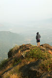 Giovane che sta sulla cima di una montagna e che gode della vista della valle Fotografie Stock Libere da Diritti