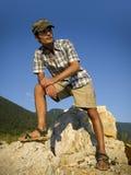Giovane che sta sulle rocce in montagne Fotografia Stock