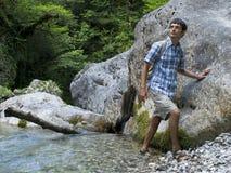 Giovane che sta vicino alla roccia nella foresta della montagna Fotografia Stock