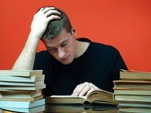 Giovane che studia, circondato dai libri Immagine Stock