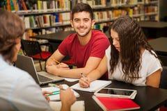 Giovane che studia con gli amici Immagine Stock