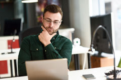 Giovane che studia con il computer portatile sullo scrittorio bianco Fotografie Stock Libere da Diritti