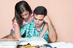 Giovane che studia con sua figlia che lo abbraccia fotografia stock libera da diritti