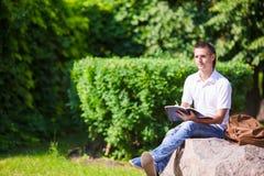Giovane che studia per l'esame dell'istituto universitario in parco Fotografia Stock Libera da Diritti