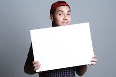 Giovane che tiene carta in bianco in uno studio Immagini Stock Libere da Diritti