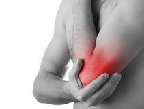 Giovane che tiene il suo gomito nel dolore, Fotografia Stock