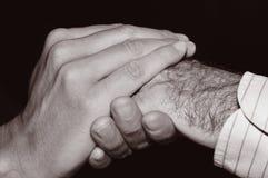 Giovane che tiene la mano di un uomo anziano, in bianco e nero Immagine Stock Libera da Diritti