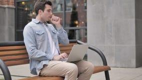 Giovane che tossisce mentre lavorando al computer portatile all'aperto stock footage
