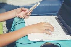 Giovane che usando l'ufficio dello Smart Phone del cellulare e del computer portatile a casa per lavorare con successo fotografia stock