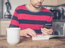 Giovane che usando Smart Phone e lettura Fotografie Stock Libere da Diritti