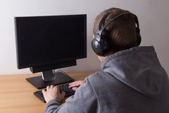 Giovane che usando un computer e una musica d'ascolto Immagine Stock Libera da Diritti