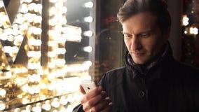 Giovane che utilizza smartphone su una via urbana nella sera che sta stanza frontale di negozio vicina video d archivio