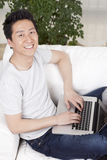 Giovane che utilizza un computer portatile nel sofà Fotografia Stock