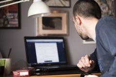 Giovane che utilizza un computer portatile nella sua stanza di studio Immagini Stock Libere da Diritti